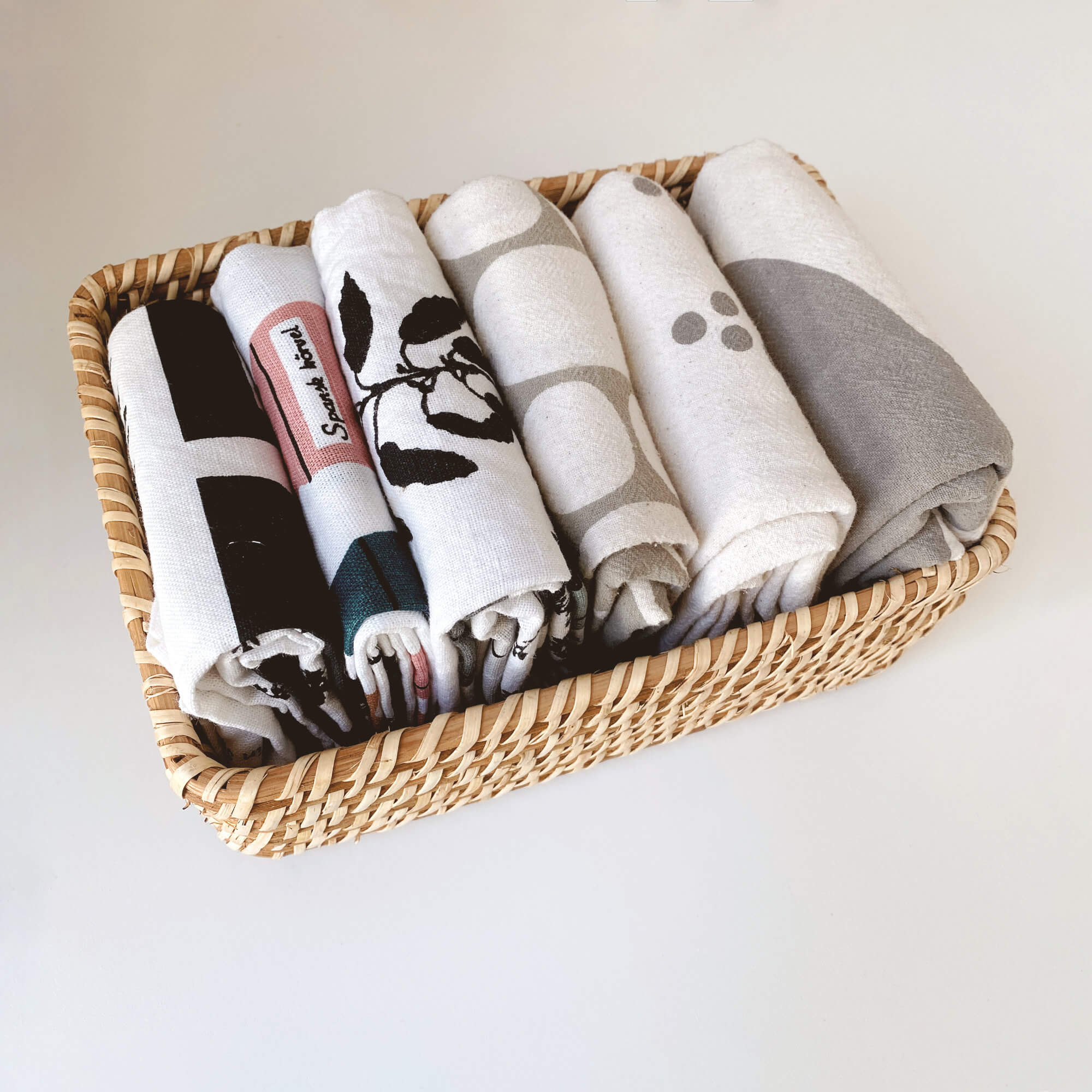 Neatly Folded Tea Towels In A Woven Bamboo Basket Using The KonMari Method Of Tidying