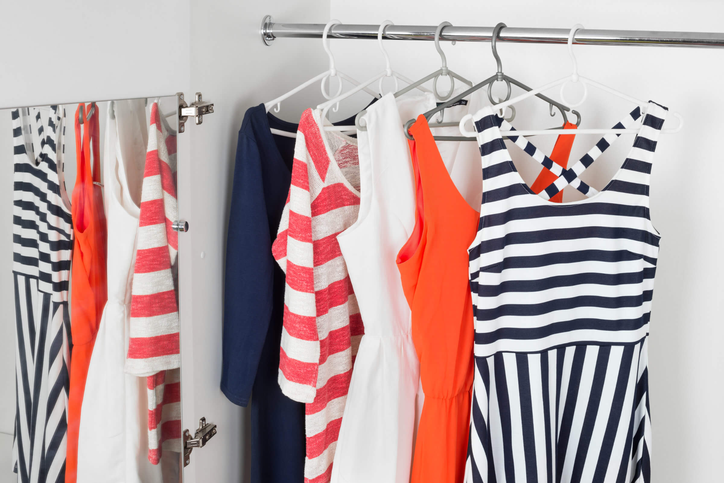 Colourful Dresses And Striped Women's Clothing Hanging On A Rail