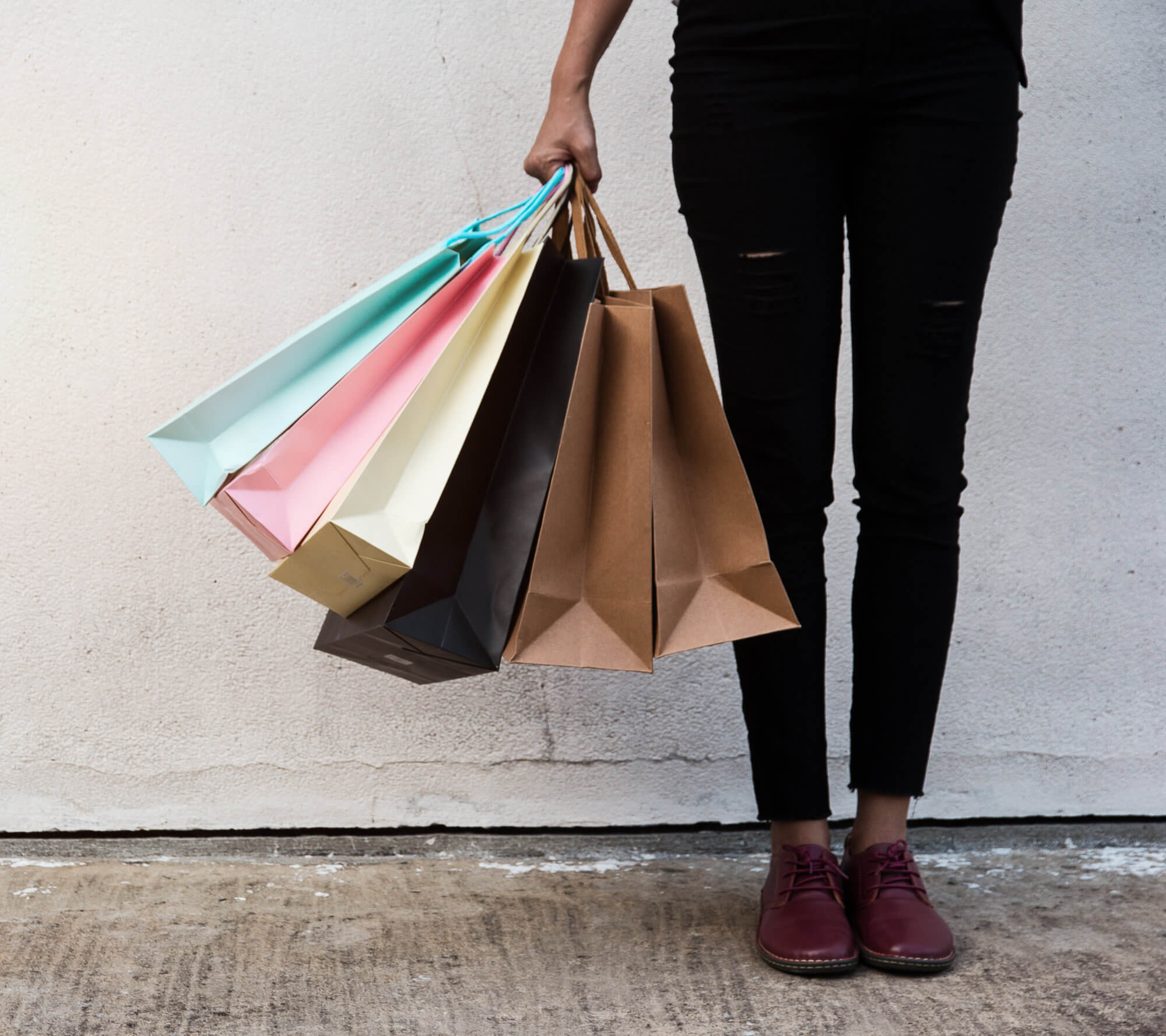 Black Woman Standing In Front Of Modern Concrete Wall Holding Colourful Shopping Bags
