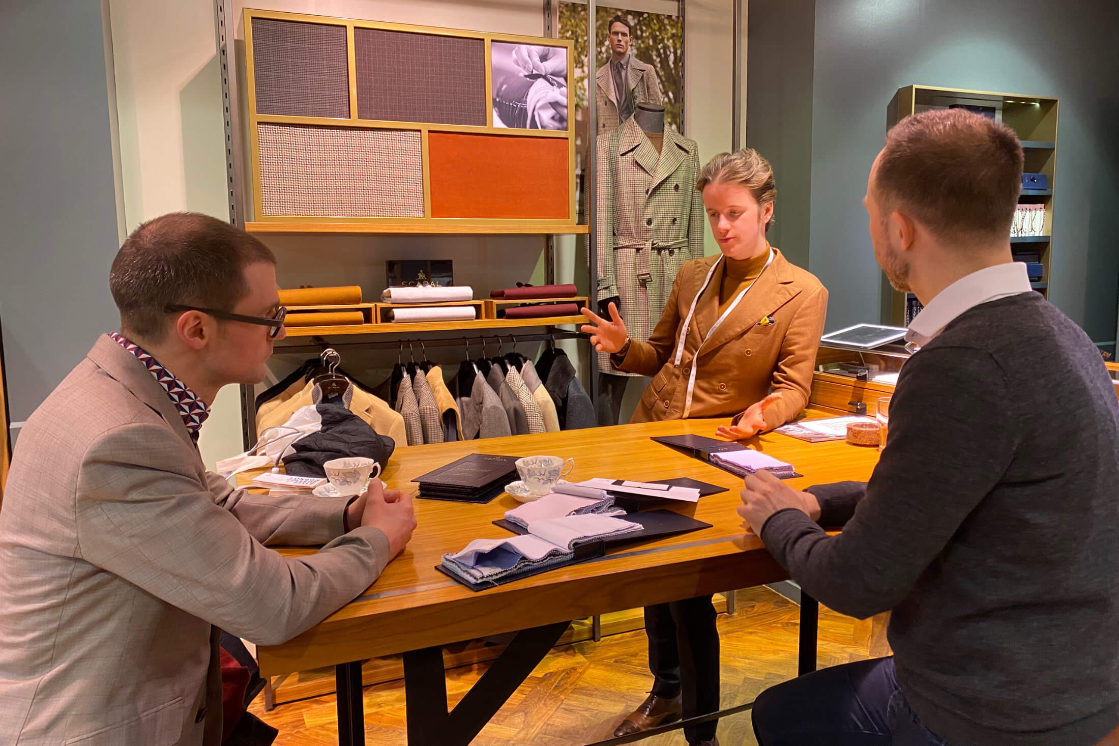 Two Men Looking Through Luxurious Fabrics With Tailor Tommy Raban For Made-To-Measure Wedding Suits At Savile Row's Scabal