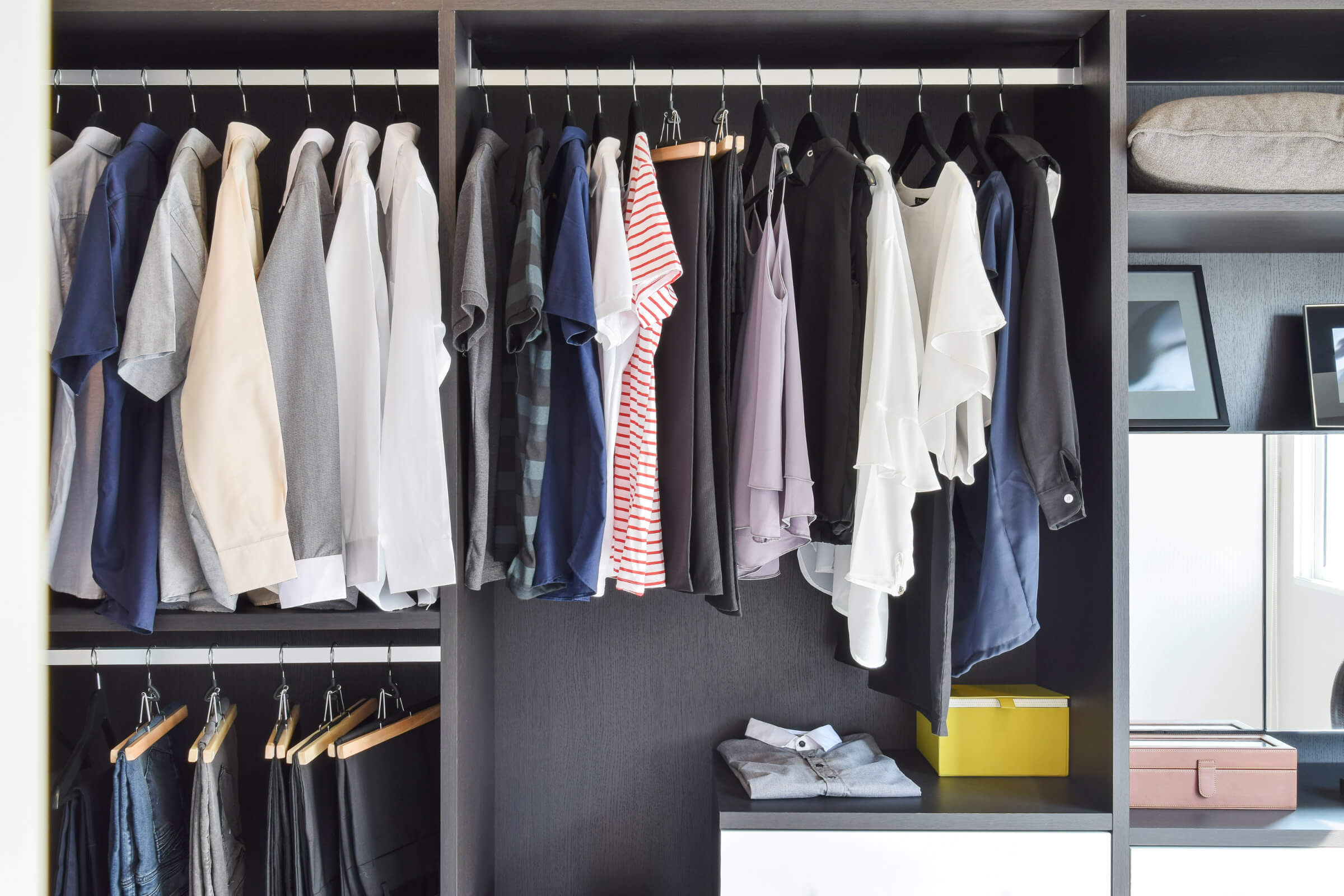 A Tidy Wardrobe Solution - Men's And Women's Clothes Hanging By Colour With A Couple Pieces Neatly Folded Underneath