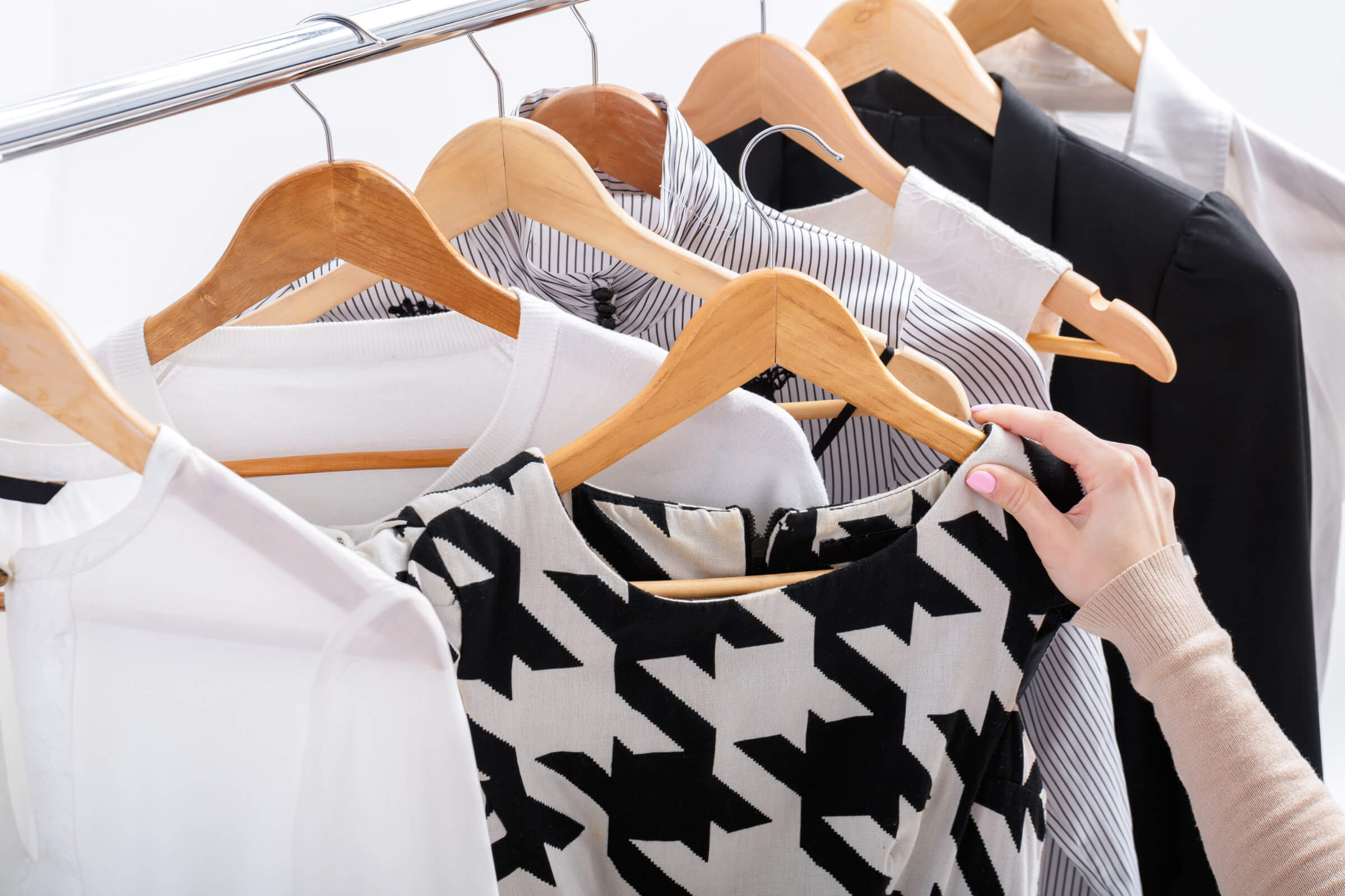 Woman Selecting Monochrome Houndstooth Dress From Rail - Always A Good Choice