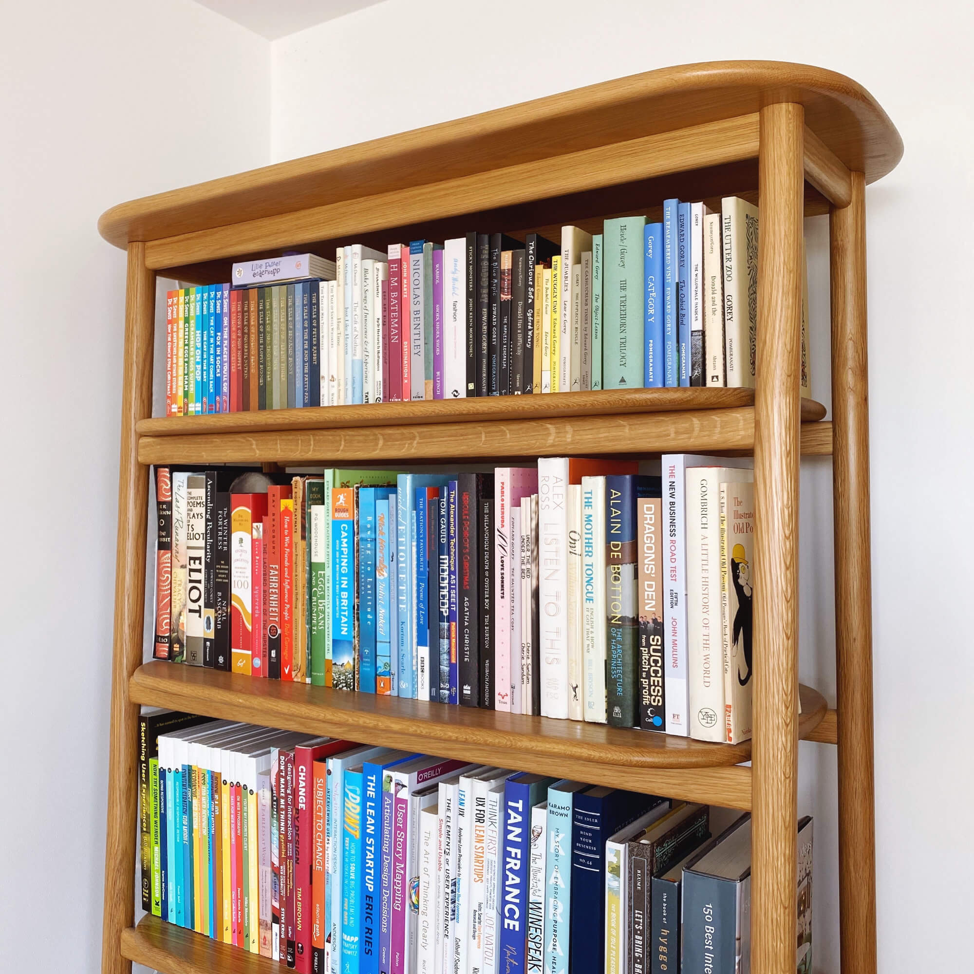 KonMari Tidying - Category Two: Books. View Of An Oak Scandi Style Bookcase Full Of Books Categorised By Colour