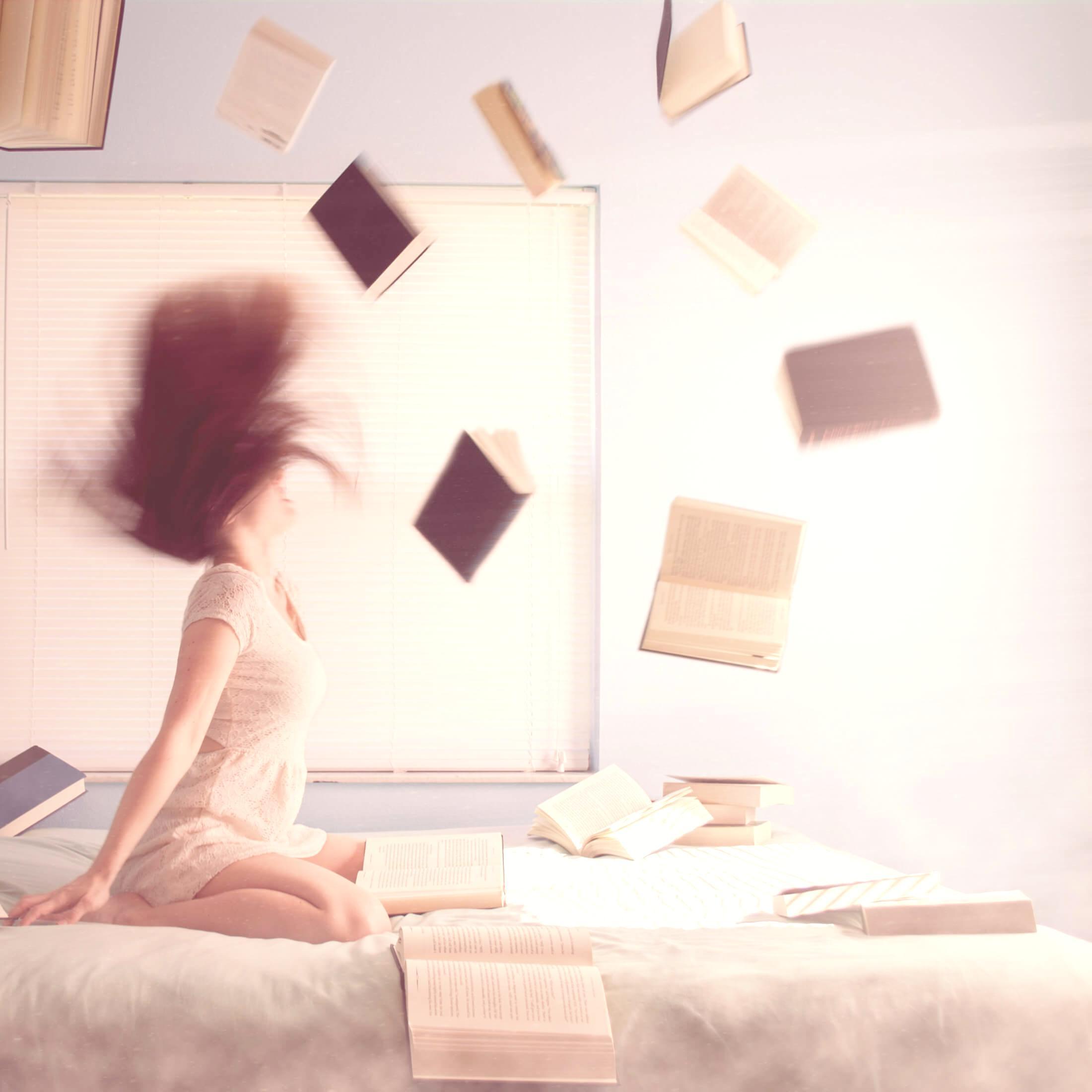 KonMari Method - Wake Up Your Books. Woman Sitting On Bed With Books Floating Like Magic. Photo by Lacie Slezak on Unsplash.