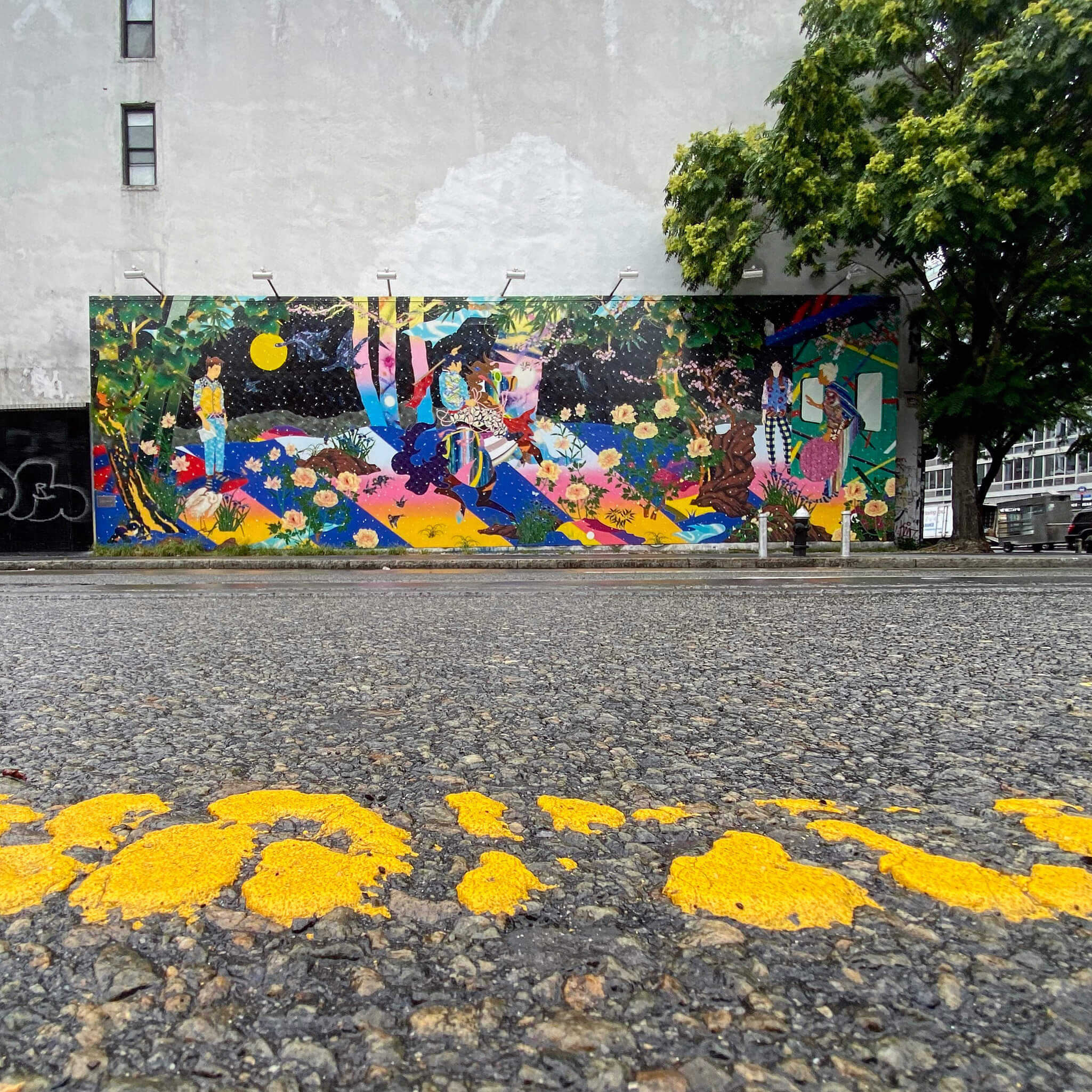 Colourful Street Art Photography by Sarah Sansom - Worn yellow writing on pavement reflects flowers in street art pic