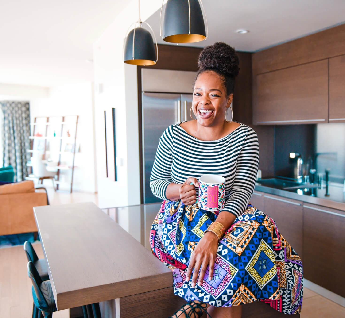 Entrepreneur Apryl Thatch, smiling and colourfully dressed, sitting on a kitchen table