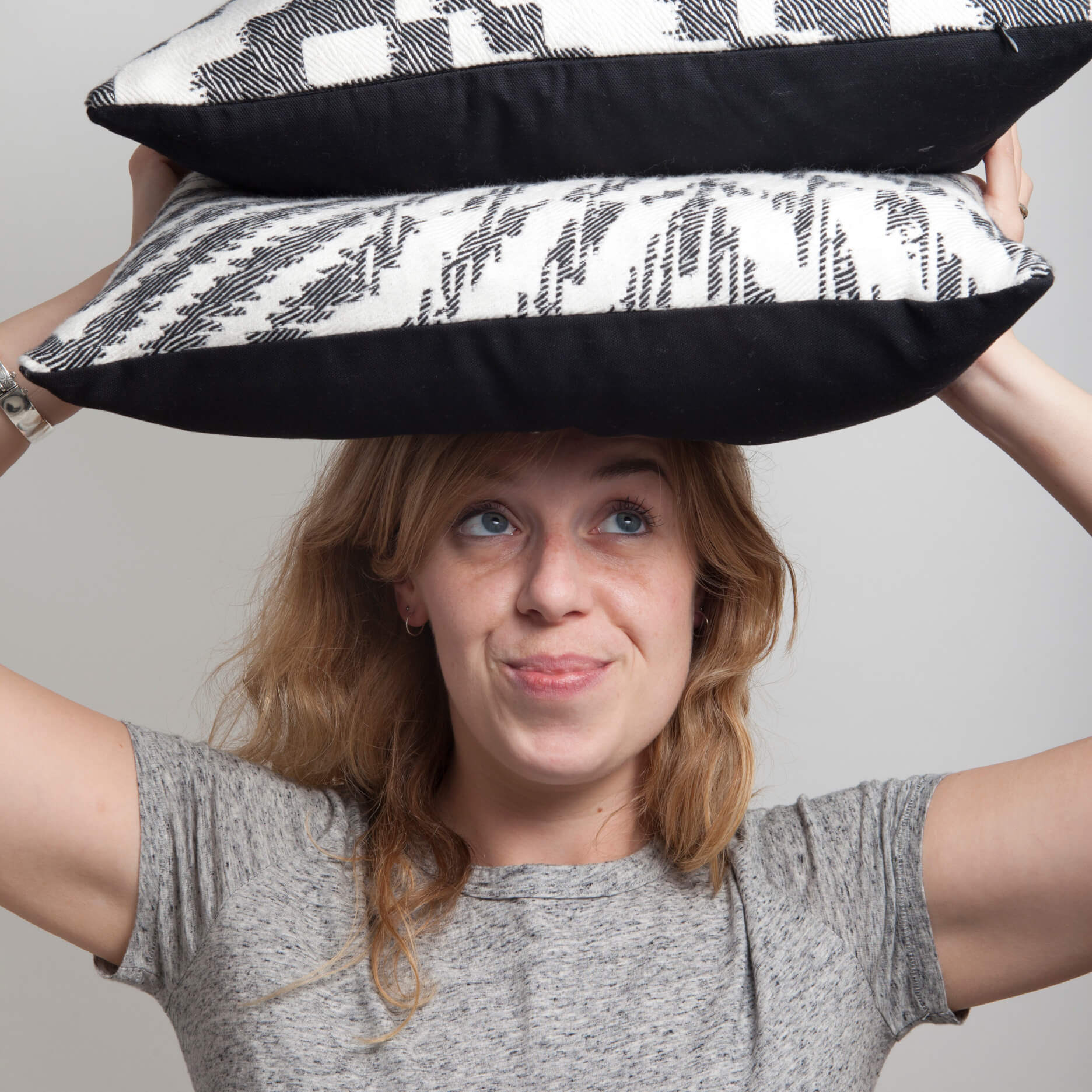 Textile Designer Beatrice Larkin Holding A Couple Of Her Bold Monochrome Cushions Above Her Head