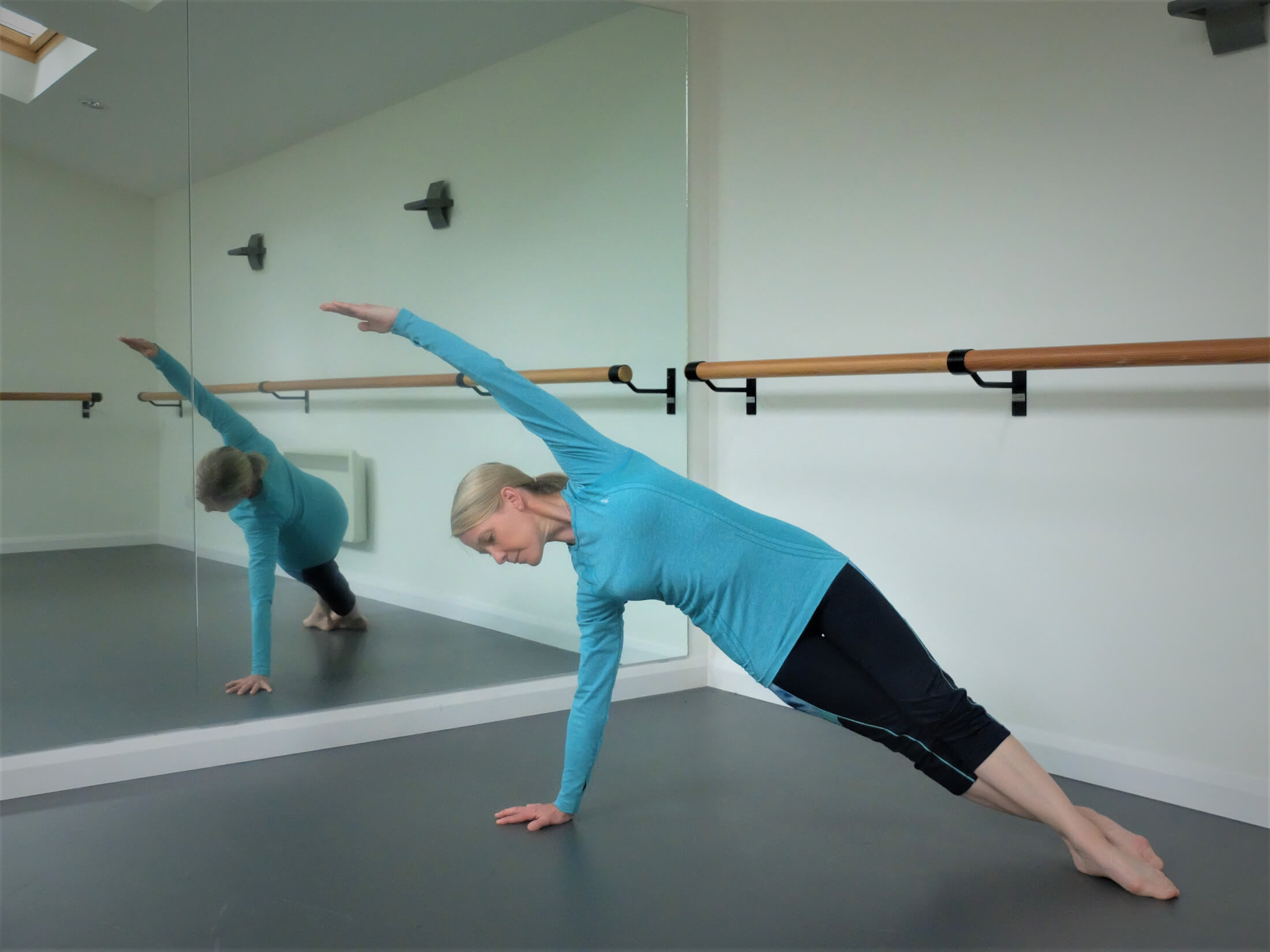 Heather Craig doing a side stretch in a dance studio
