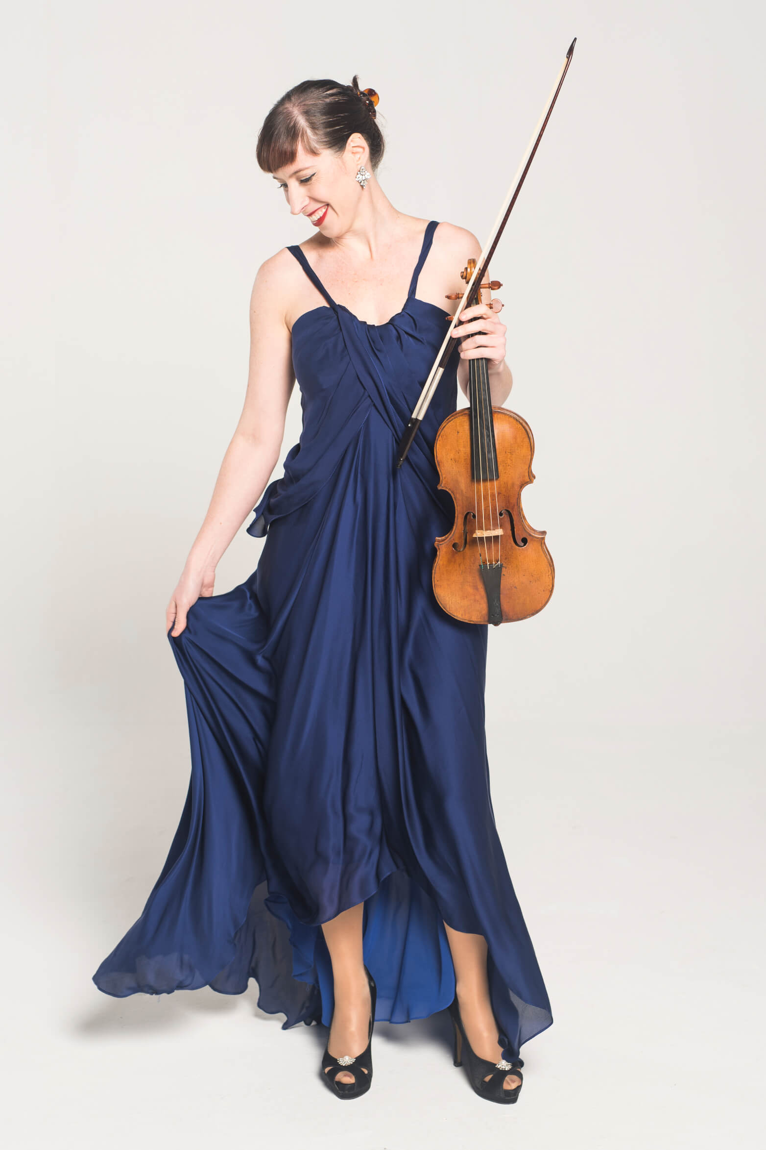 Madeleine Easton wearing a fabulous deep blue dress and holding her violin.
