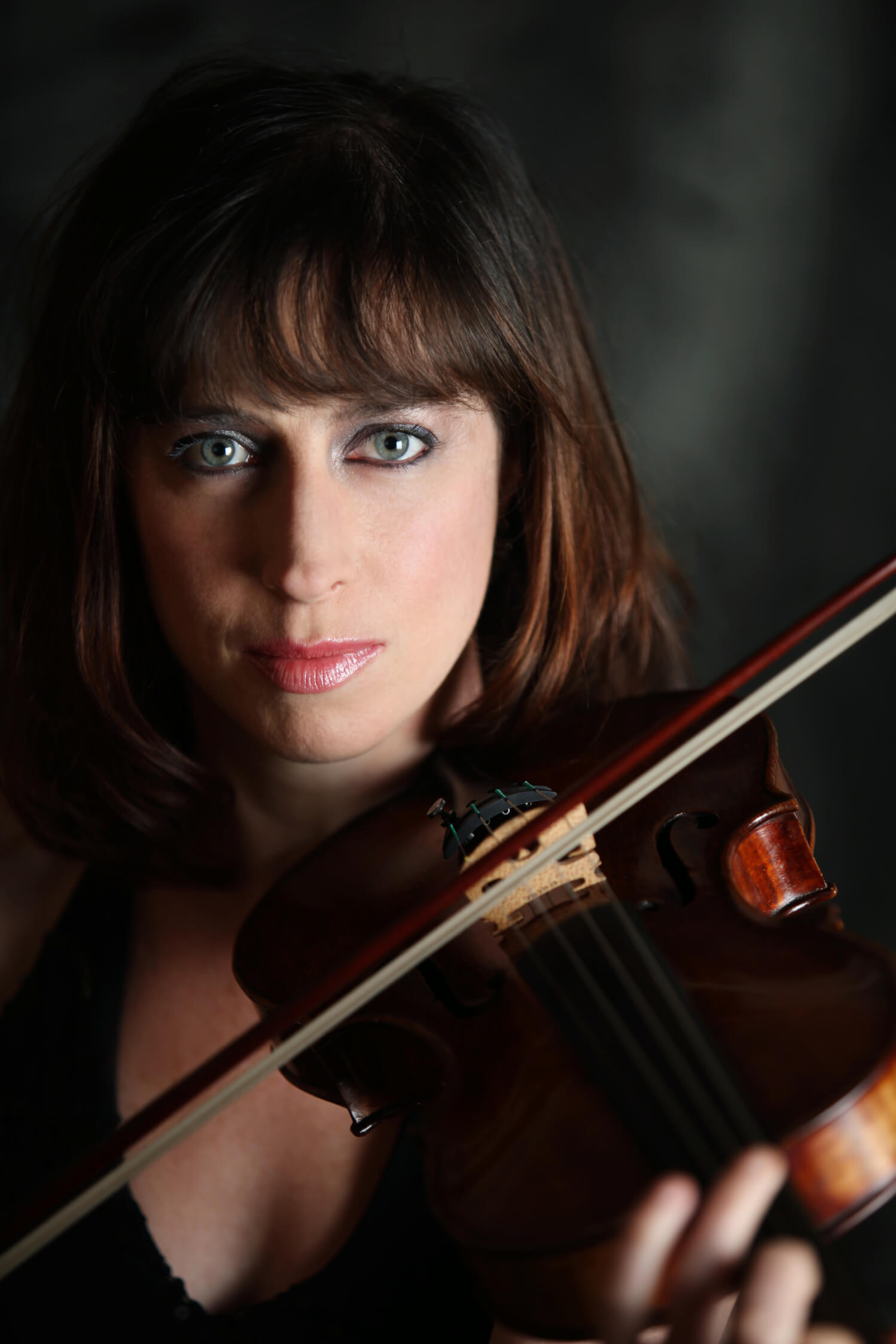 Madeleine Easton holding her violin and looking directly at the camera.