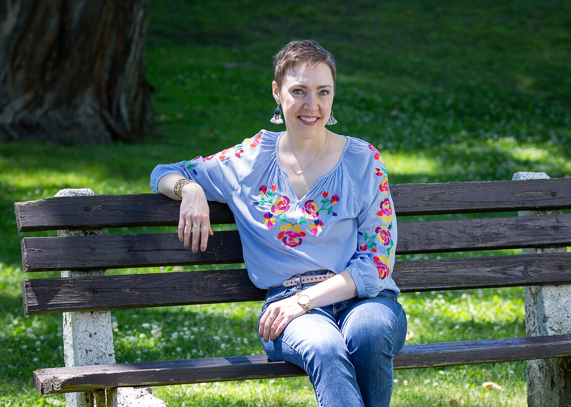 Life coach Penny Casselman sitting on a wooden bench in a lush green park.