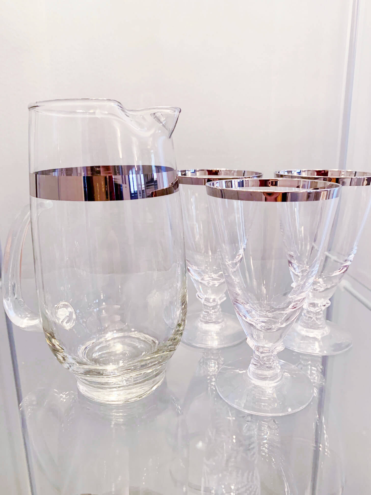 Silver rimmed cocktail glasses and pitcher.