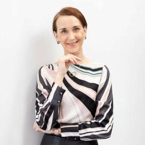 Success and Business Coach Dijana Llugolli wearing a smart striped, silky top
