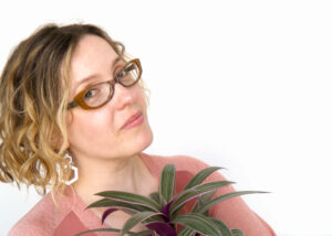 Portrait of Alexandria Lawrence wearing a dusty pink top and holding a pinky purple plant.