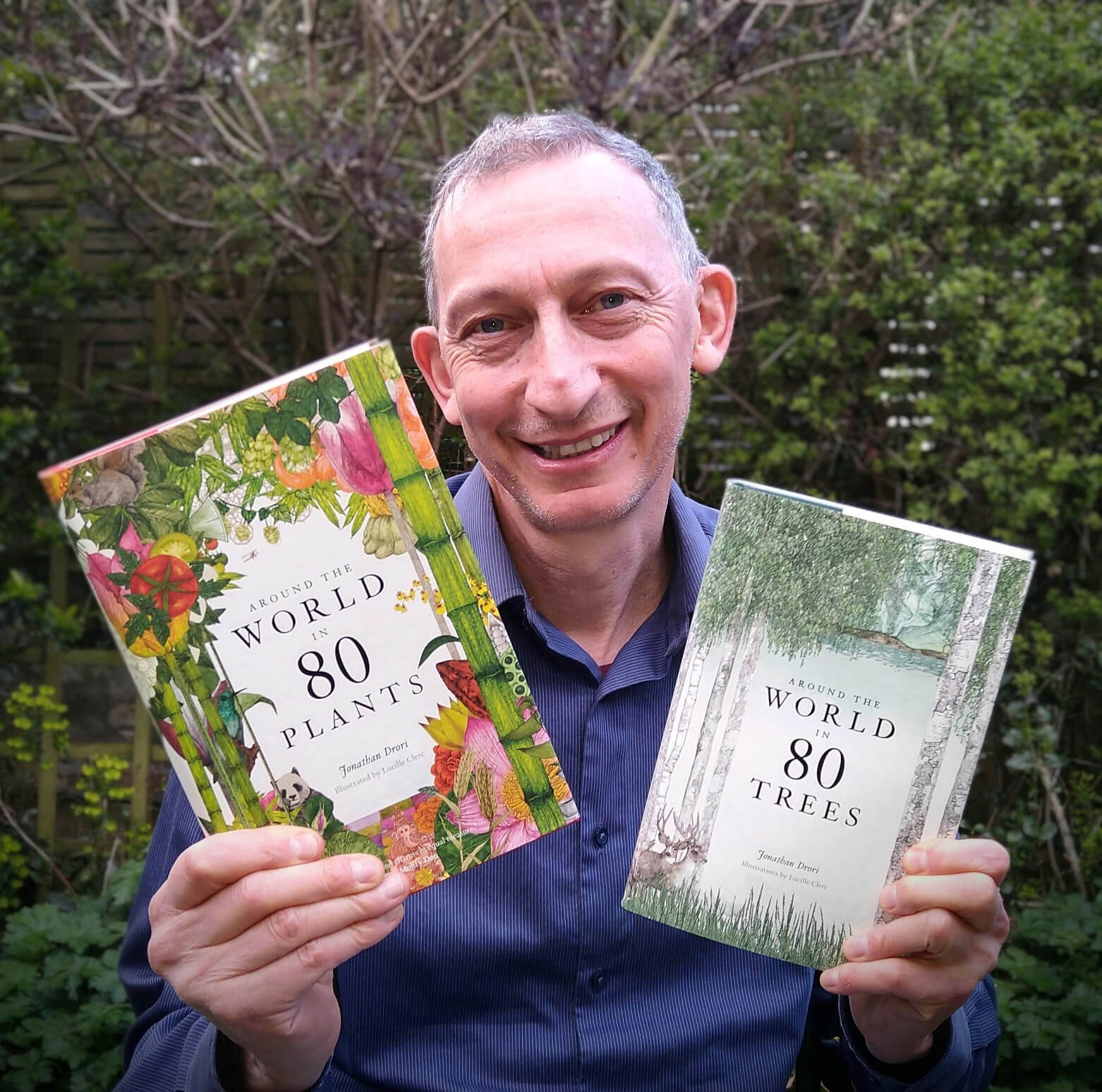 Plant enthusiast and author Jonathan Drori smiling and holding his books Around the World in 80 Trees and Around the World in 80 Plants