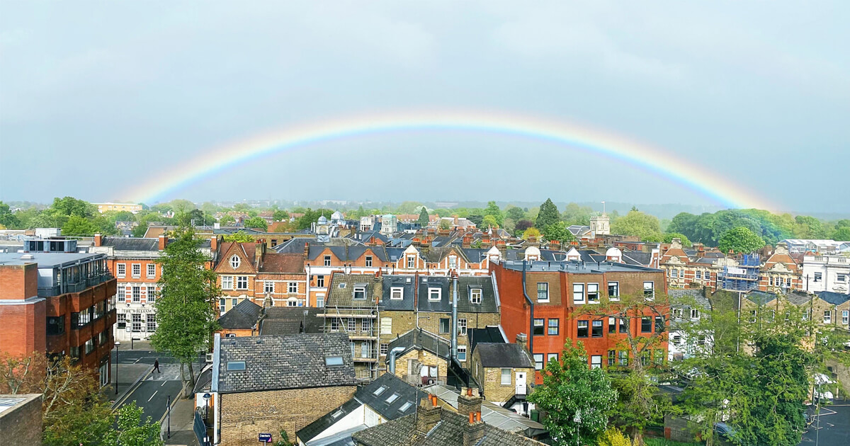 Magnificent, picture-perfect rainbow. View from our kitchen window with little houses and trees.