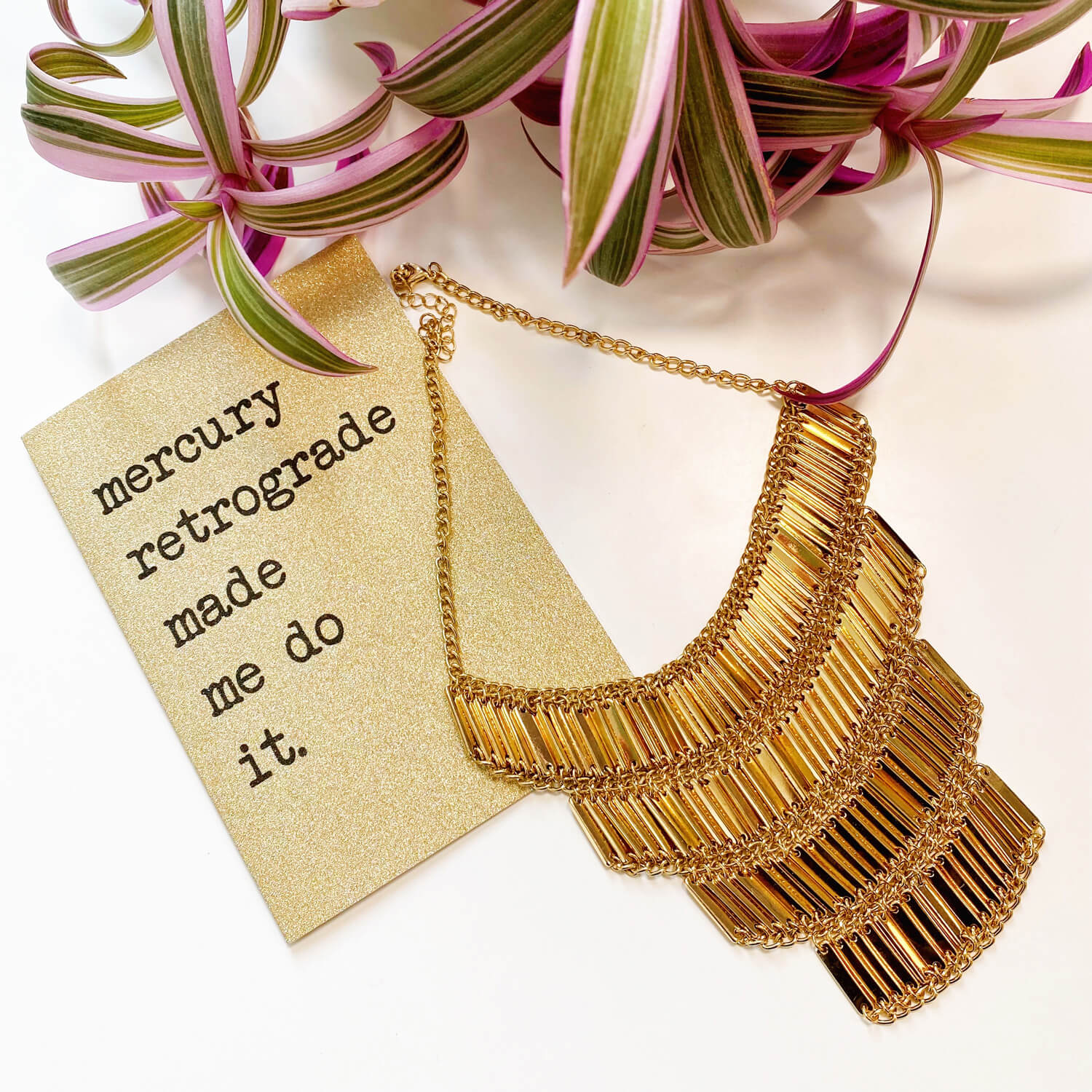 """Glittery gold greeting card that says 'mercury retrograde made me do it"""" pictured next to a sparkly gold necklace and fashionable pink plant"""