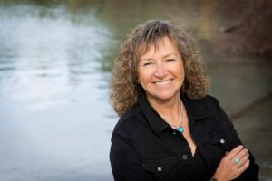 Trauma & EFT Tapping Specialist Sherry Lukey smiling in front of a gleaming lake